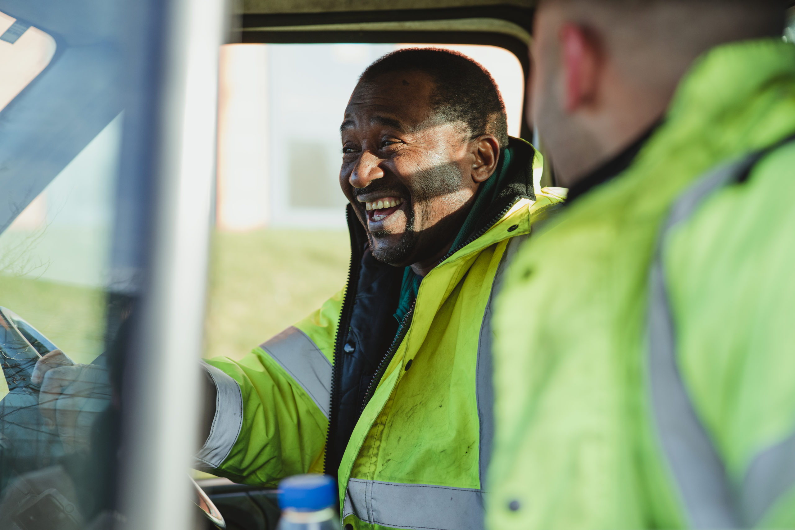 Senior man and his son are laughing and talking together in their work van.